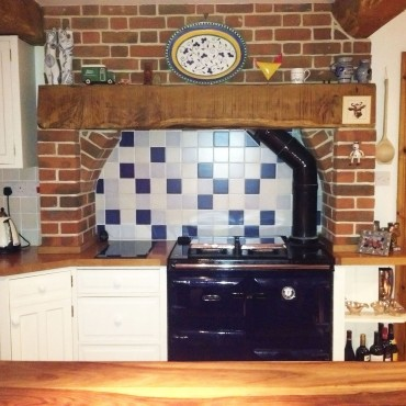 These inexpensive tiles in 2 shades of blue and an off-white transformed the wall under the mantle and worked beautifully with the dark blue Rayburn