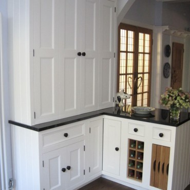 These built-in oak trays and wine rack not only add interest and functionality, but also tie in with the wooden floor